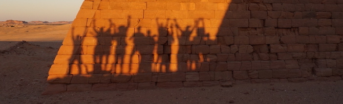 Schattenriss der Exkursionsteilnehmerinnen vor einer Pyramide am Jebel Barkal Slider.JPG